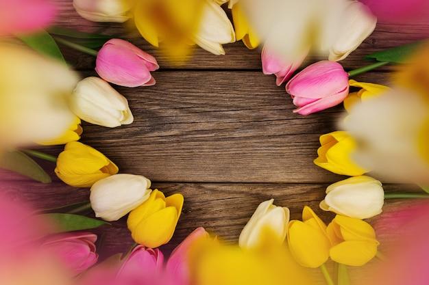 Bela composição com tulipas coloridas com espaço de cópia na madeira