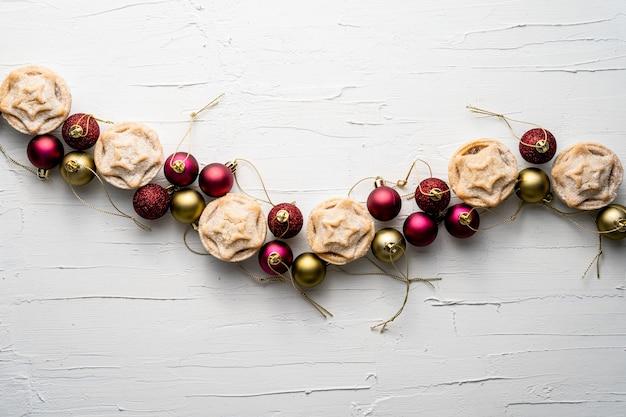 Bela composição de bolas de árvore de natal e tortas de carne moída em uma superfície branca