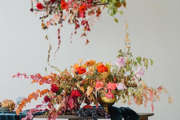 Bela composição de flores com flores laranja e vermelhas de outono e frutas vermelhas