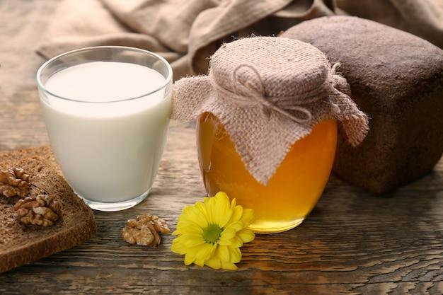 Bela composição de mel dourado e leite na mesa de madeira