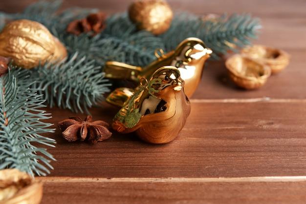Bela composição de natal com pássaros dourados, na mesa de madeira