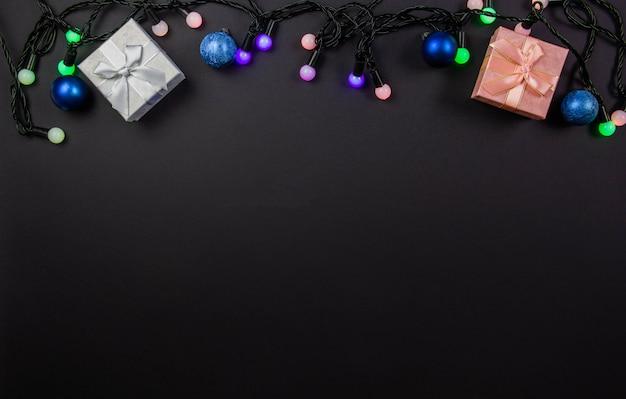 Bela composição de natal em um fundo preto com caixas de presente de natal e luzes brilhantes guirlanda multicoloridas. vista de cima. copie o espaço