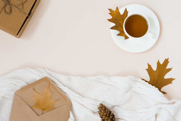 Bela composição de outono com uma xícara de chá. folhas de outono, caixa de presente kraft, um envelope e um cobertor de malha