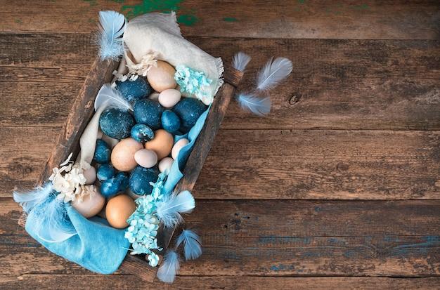 Bela composição de páscoa com ovos pintados e naturais em um fundo de madeira.