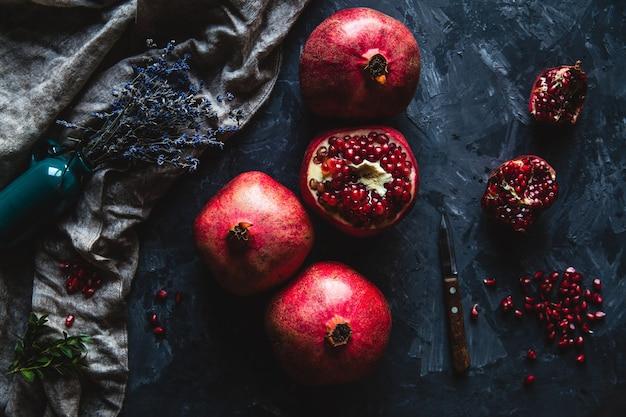 Bela composição de romãs em um fundo escuro com uma toalha, alimentação saudável, frutas