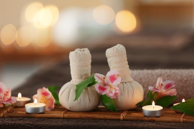 Bela composição de spa com bolas de compressa de massagem e velas no fundo desfocado