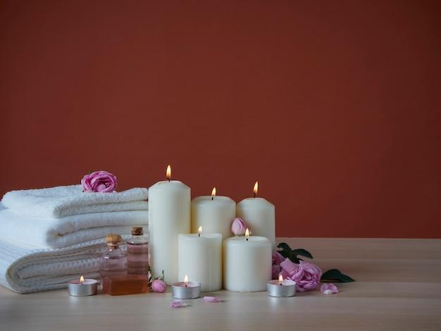 Bela composição de spa com queima de velas perfumadas e óleo aromático, rosas cor de rosa na mesa de madeira
