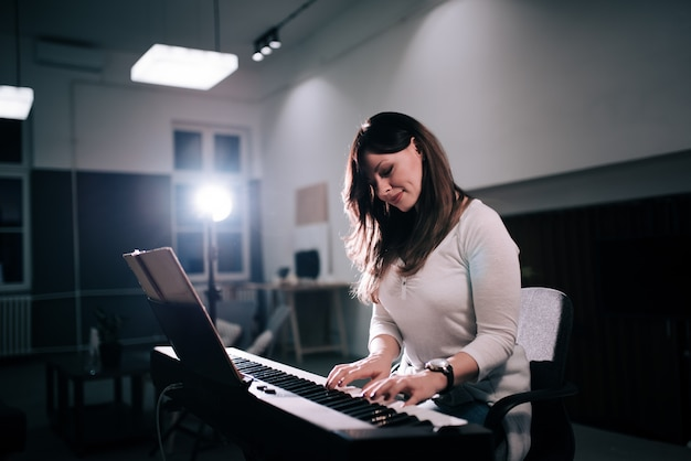 Bela compositor feminino tocando piano.