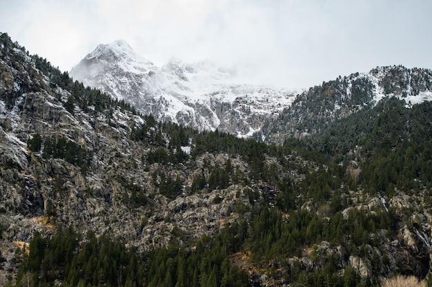Bela cordilheira coberta de neve envolta em névoa