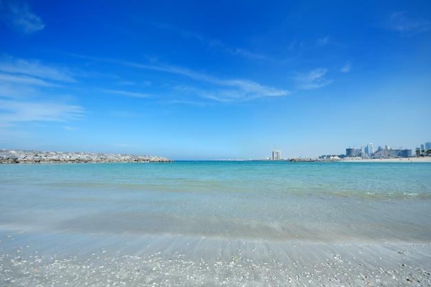 Bela costa marítima e uma cidade moderna construída no horizonte.