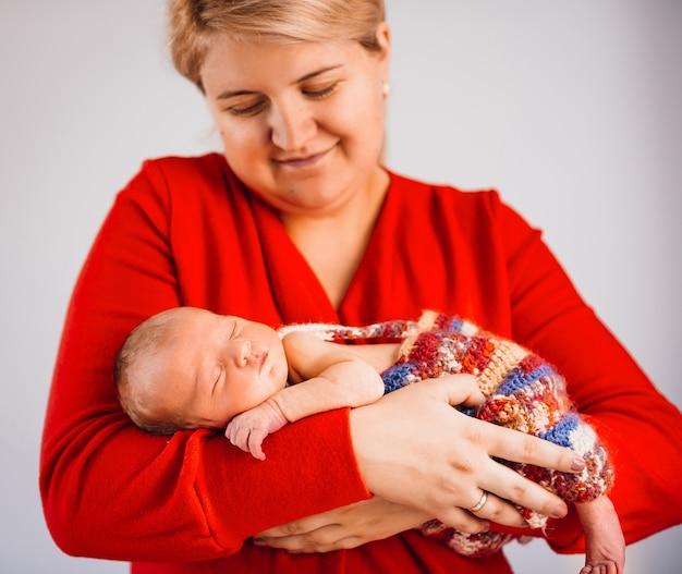 Bela criança dorme nos braços da mãe