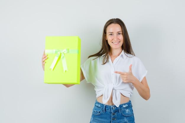 Bela dama apontando para a caixa de presente em blusa branca, calça jeans e olhando alegre. vista frontal.