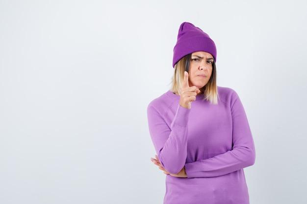 Bela dama apontando para cima em suéter, gorro e olhando confiante, vista frontal.