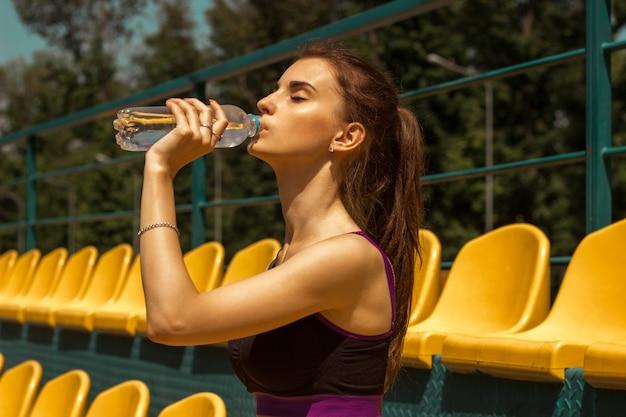 Bela dama atlética bebe água de uma garrafa no close-up do stade