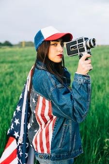 Bela dama com câmera retro, ficando no campo