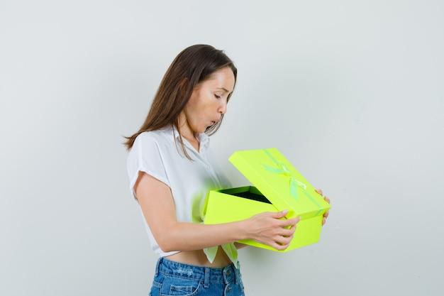 Bela dama de blusa branca, abrindo a caixa de presente amarela e olhando impaciente, vista frontal.