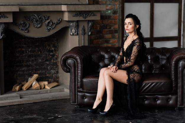 Bela dama de calcinha preta elegante e penhoar deitada na cama no quarto dela.