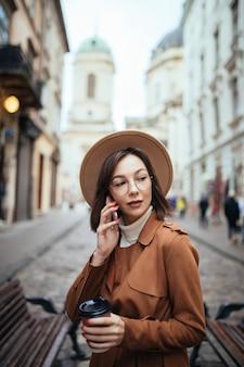 Bela dama de casaco marrom, falando no telefone celular, caminhando ao ar livre em dia frio de outono