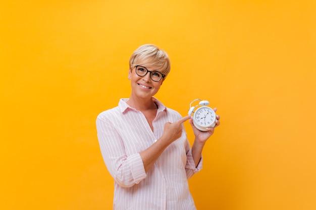 Bela dama de óculos olha para a câmera e aponta para o despertador em fundo laranja