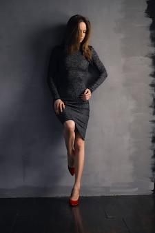 Bela dama de vestido encostada na parede com o joelho dobrado em sapatos de verniz vermelho olhando para o chão