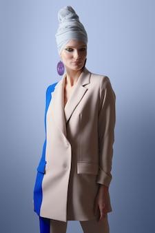 Bela dama em terno de cor dupla e turbante na cabeça