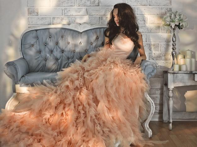 Bela dama em vestido lindo couture no sofá