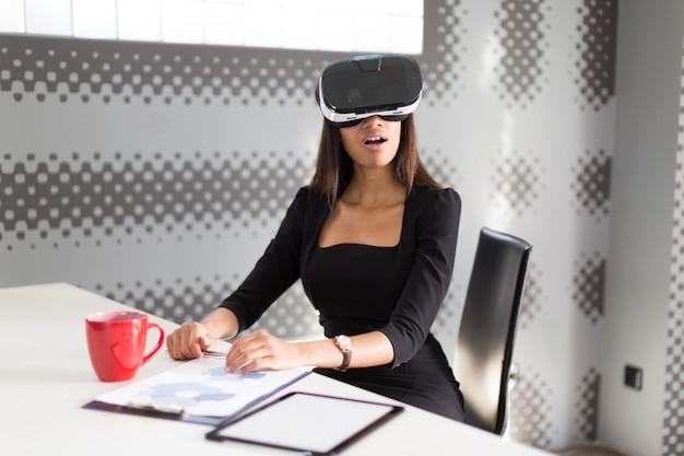 Bela dama jovem negócios em preto forte suite sentar na mesa de escritório em vidros vr