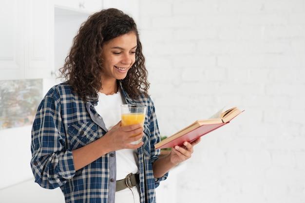 Bela dama lendo um livro e segurando um copo de suco