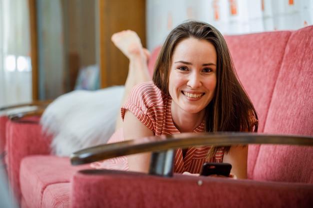 Bela dama mentindo e sorrindo em vestido listrado rosa na sala em um sofá