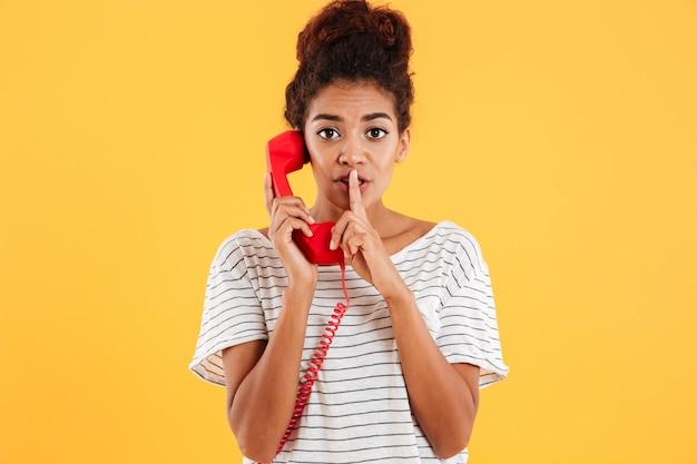Bela dama mostrando o gesto de silêncio enquanto fala no aparelho vermelho