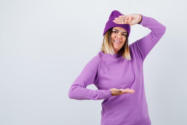 Bela dama mostrando sinal de tamanho grande em suéter, gorro e olhando alegre, vista frontal.