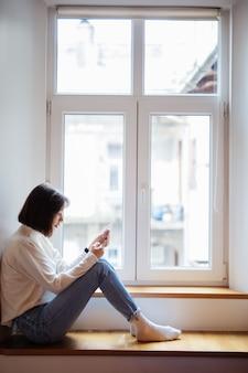 Bela dama no quarto sentado perto da janela em roupas casuais com telefone