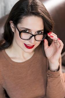 Bela dama olhando por cima de óculos pretos na câmara