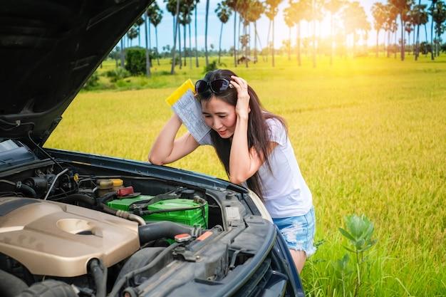 Bela dama, verificando seu carro quebrado perto da estrada durante a sua viagem de férias.