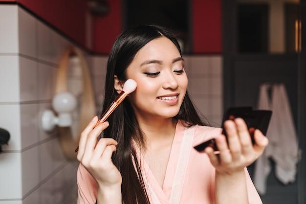Bela dama vestida de robe de seda rosa com sorriso fazendo maquiagem no banheiro