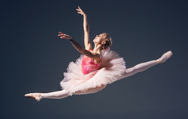 Bela dançarina de balé feminina em um fundo cinza