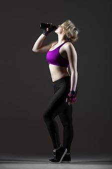 Bela dançarina esportiva bonita bebendo