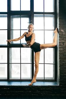 Bela dançarina loira atlética e desportista com belo corpo musculoso, fazendo exercícios de alongamento