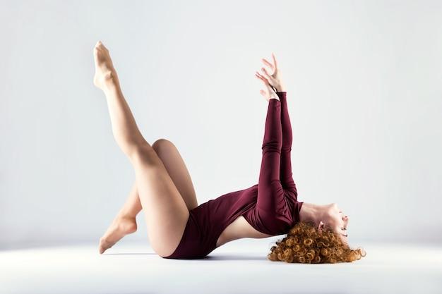 Bela dançarina profissional bonita que dançam sobre o fundo branco.