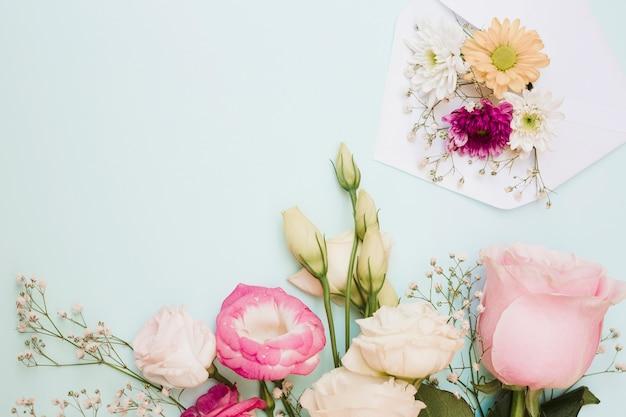 Bela decoração de flores frescas com envelope em fundo colorido