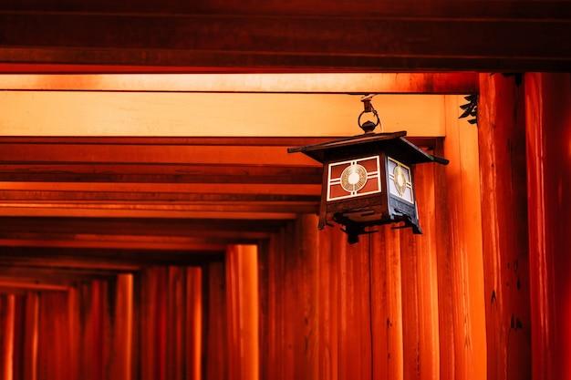 Bela decoração de lanterna nos portões torii vermelho-laranja do santuário fushimi inari taisha em kyoto, japão