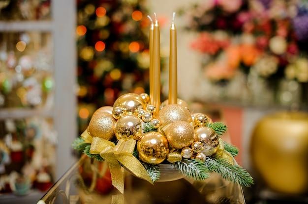 Bela decoração de mesa de natal feita de velas douradas, bolas de vidro e ramos de abeto