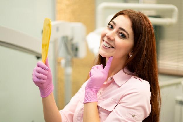 Bela dentista feminina mostra dentes saudáveis. sorrindo e segurando um espelho. odontologia e higiene bucal.