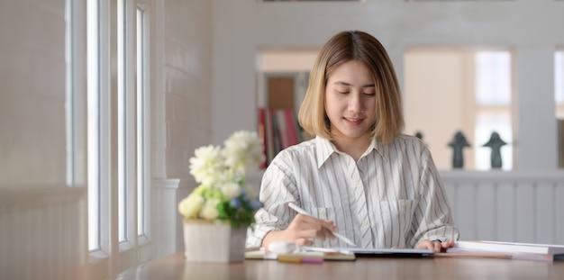 Bela designer feminino trabalhando em tablet de tela em branco no seu espaço de trabalho