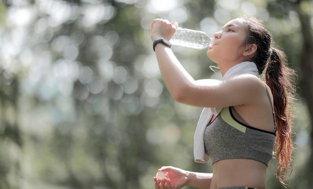 Bela desportista asiática bebendo água após treino ou exercício ao ar livre, copie o espaço.