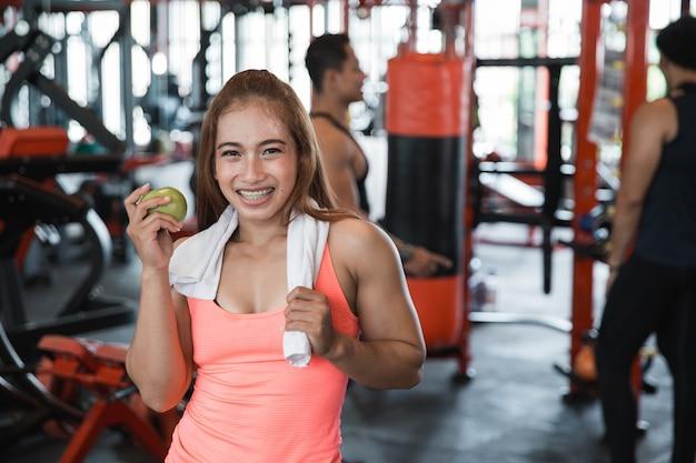 Bela desportista sorridente segurando a maçã e a garrafa de água