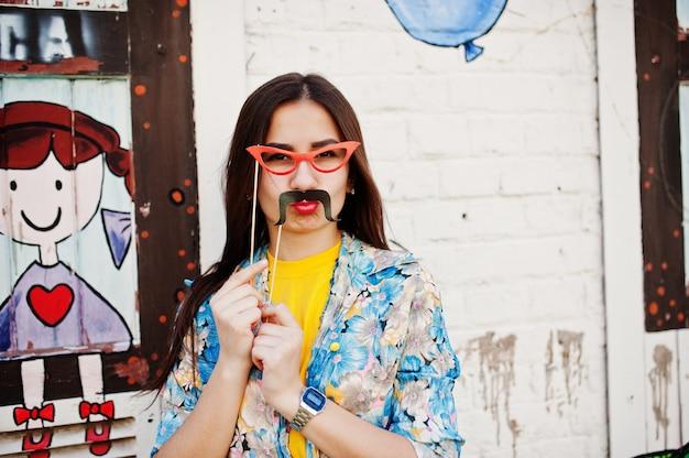 Bela diversão adolescente com óculos e bigode na vara usar camiseta amarela, perto da parede do graffiti.