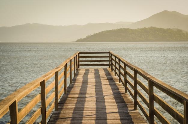 Bela doca de madeira na lagoa com vista para montanhas, vista tranquila.