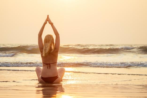 Bela e jovem mulher praticando ioga meditativa na praia