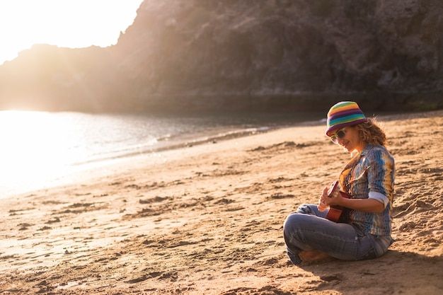 Bela e pacífica jovem sentada na praia, desfrutando de uma atividade de lazer na areia, tocando uma guitarra ukulele, sorrindo perto do oceano para férias e o conceito de liberdade